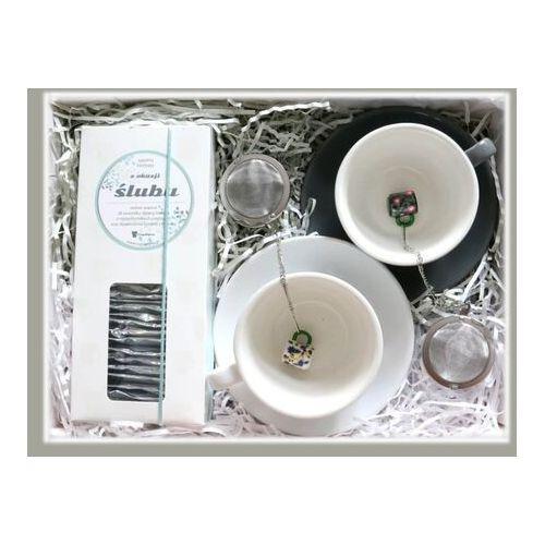 Zestaw prezentowy z okazji ślubu WSPÓLNE CHWILE. Zestaw 28 saszetek z herbatą w eleganckim dyspenserze, klasyczna szara i biała filiżanka ze spodkiem oraz dwa zaparzacze z uroczą zawieszką